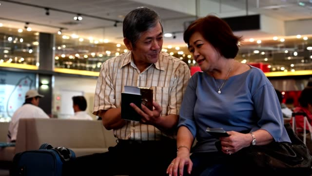 cheerful senior couple talking in an airport lounge - ethnicity stock videos & royalty-free footage