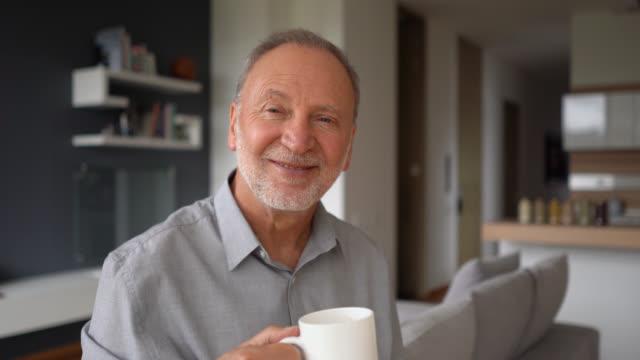 vídeos de stock, filmes e b-roll de homem sênior alegre que aprecia um café em casa ao enfrentar o sorriso da câmera - colômbia