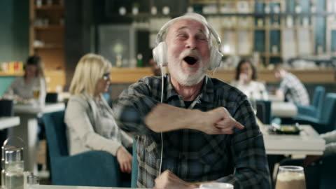 cheerful senior man listening music on headphones in restaurant - one senior man only stock videos & royalty-free footage