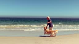 Cheerful senior man playing with dog