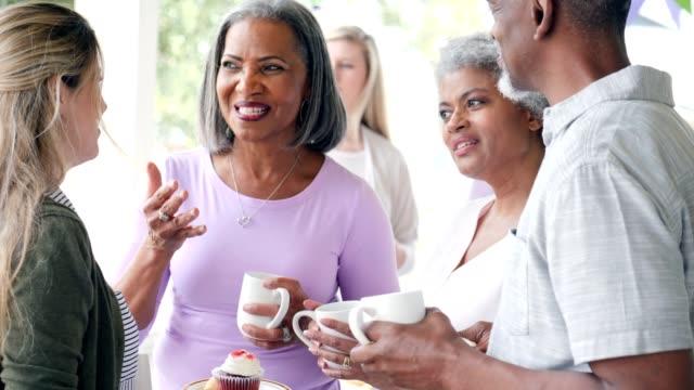 fröhliche senior frau besucht charity-dessert-event mit freunden - benefiz veranstaltung stock-videos und b-roll-filmmaterial