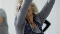 Cheerful Senior Woman in Dynamic Stretching Class