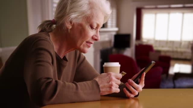 vídeos y material grabado en eventos de stock de cheerful senior woman using credit card and smart phone to make payment online - pago por móvil