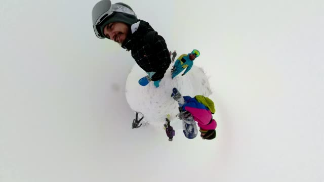 Cheerful snowboarders on a snowy mountain