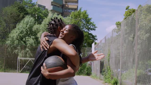 fröhliche streetball-spieler umarmen sich auf dem platz - body positivity stock-videos und b-roll-filmmaterial