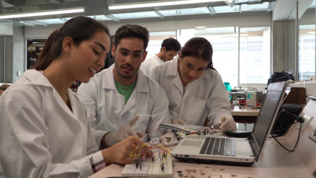cheerful students at an electronics class working on an experiment while talking very happy - post secondary education stock videos & royalty-free footage