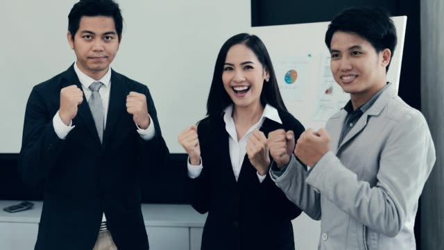 Cheerful successful group business people rejoycing with fists raised, achievement , slow motion
