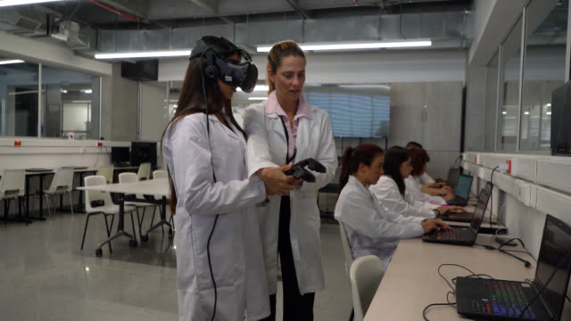 cheerful teacher adjusting a vr headset on female student during an experiment at college - cyberspace stock videos & royalty-free footage