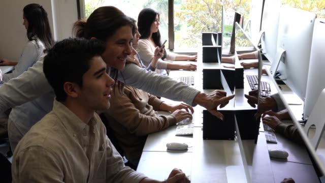 vídeos de stock, filmes e b-roll de professor alegre ajudando um jovem estudante do sexo masculino com uma pergunta na aula it, apontando para a tela - entusiástico