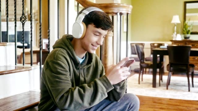 cheerful teenage boy plays game on mobile phone - one teenage boy only stock videos & royalty-free footage