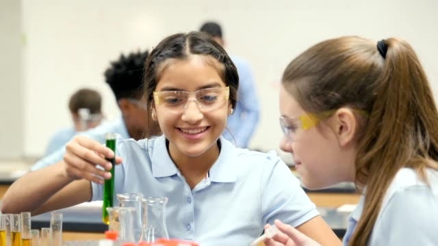 cheerful teenage female chemistry lab partners enjoy conducting experiment - curiosity stock videos & royalty-free footage