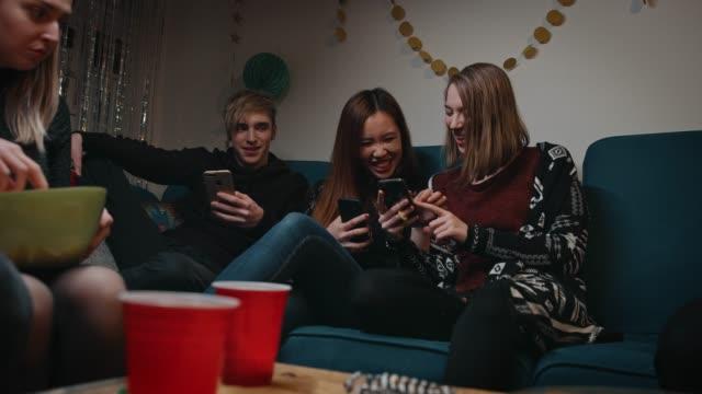 fröhliche teenager freunde mit handys in partei - zwischenmahlzeit stock-videos und b-roll-filmmaterial
