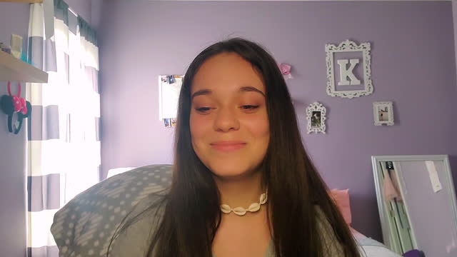 a cheerful teenage girl adds to discussion while in a zoom class from home - webcam video stock e b–roll