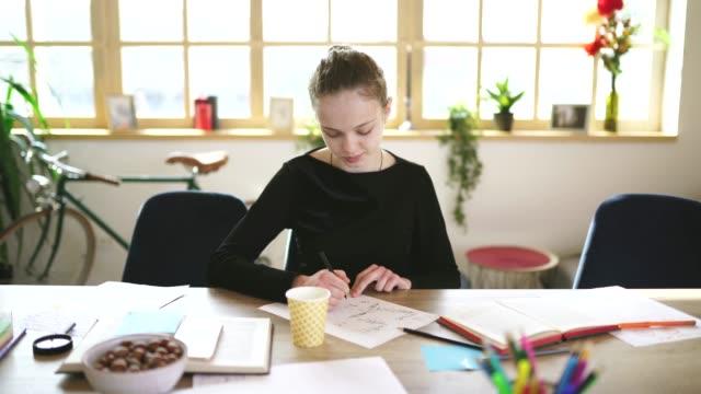 vidéos et rushes de dessin gai de fille adolescente dans la salle de classe - cours de mathématiques