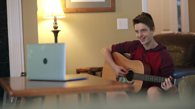 cheerful teenager learning to play guitar at home via video call - one teenage boy only stock videos & royalty-free footage