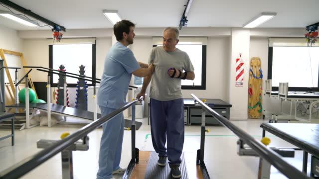 vídeos de stock, filmes e b-roll de terapeuta alegre que ajuda o paciente sênior com uma caminhada da cinta de mão que inclina-se em barras paralelas durante a terapia física - physical injury