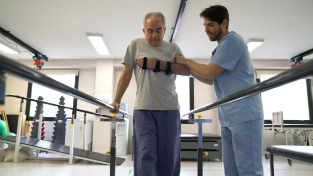 glad terapeut med senior patienten hålla honom medan han går med hjälp av parallella barer - barr bildbanksvideor och videomaterial från bakom kulisserna