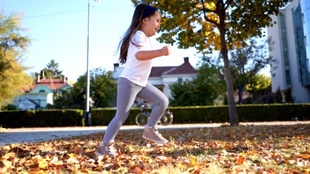 cheerful toddler girl enjoying autumn in a city park - side view stock videos & royalty-free footage
