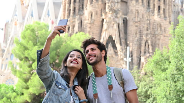 cheerful travelers taking selfie in front of sagrada familia - hand sign stock videos & royalty-free footage