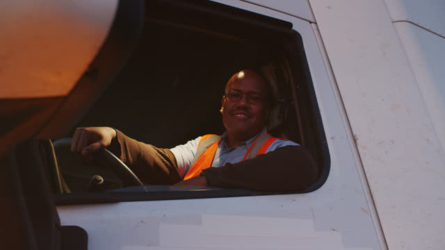 vídeos y material grabado en eventos de stock de cheerful truck driver smiling at camera from inside cab - camionero