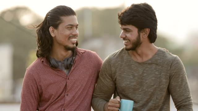 vídeos de stock e filmes b-roll de cheerful two young friends having conversation - amizade masculina