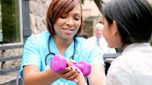 fröhliche freiwilligen physiotherapeuten hilft jungen asiatin bei outdoor-charity-klinik - scrubs stock-videos und b-roll-filmmaterial