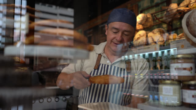 cheerful waiter grabbing a sweet pastry snack and placing it on plate at a bakery - window display stock videos & royalty-free footage