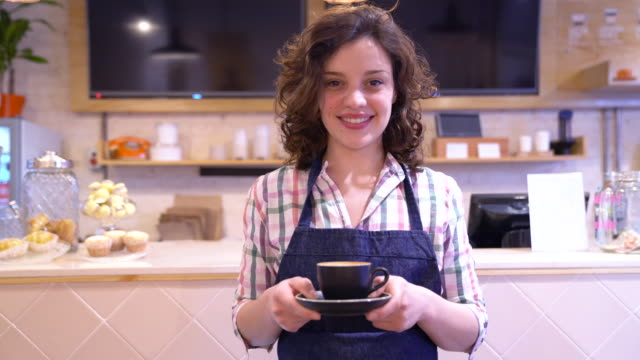 cheerful waitress at a coffee house offering a coffee to camera looking very happy - catering occupation stock videos & royalty-free footage