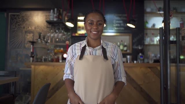 glad servitris svart etnicitet välkomna kunder med ett stort leende - öppen bildbanksvideor och videomaterial från bakom kulisserna