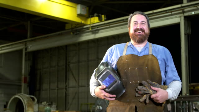 cheerful welder holding his gloves and mask - steel worker stock videos & royalty-free footage