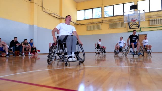 cheerful wheelchair athletes training together and having fun - wheelchair basketball stock videos & royalty-free footage
