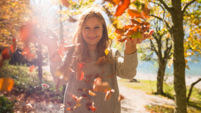 Cheerful woman at lake throwing colorful autumn leaves