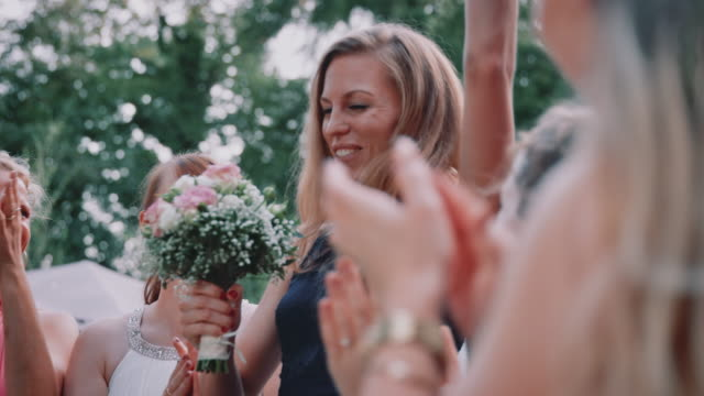 cheerful woman catching flower bouquet in wedding - bouquet stock videos & royalty-free footage