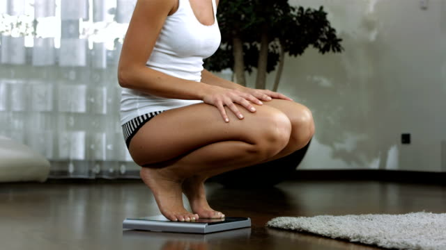 hd :dolly 陽気な女性彼女の体重を確認 - ダイエット点の映像素材/bロール