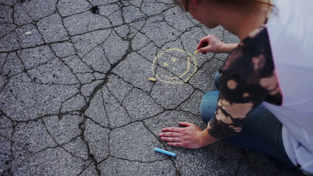 cheerful woman drawing sun with chalk on asphalt - いたずら書き点の映像素材/bロール