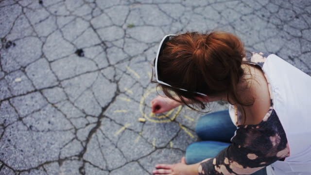 Cheerful woman drawing sun with chalk on asphalt
