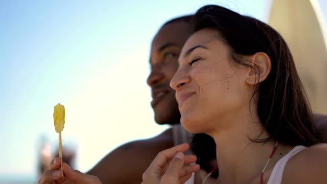 vídeos y material grabado en eventos de stock de cheerful woman eating ice cream with man at beach - helado comida dulce congelada