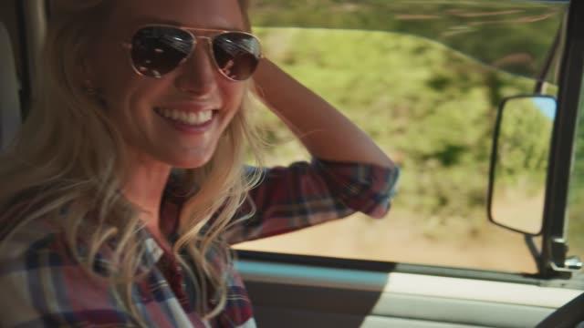 vídeos y material grabado en eventos de stock de mujer alegre disfrutando de viaje por carretera durante el verano - gafas de sol