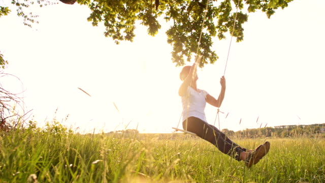 slo mo cheerful woman enjoys swinging - wellbeing stock videos and b-roll footage