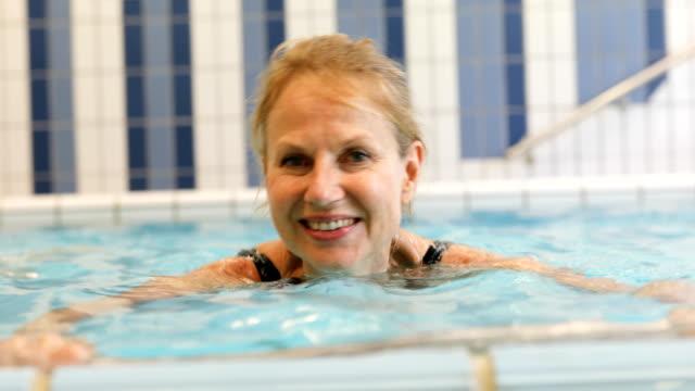 vídeos de stock e filmes b-roll de cheerful woman exercising in swimming pool - mature adult