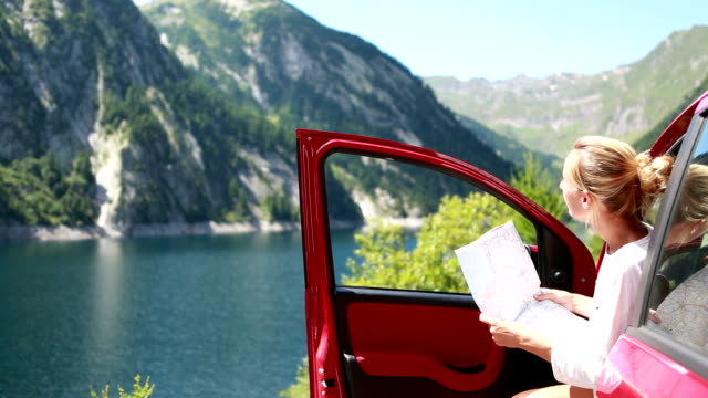 Cheerful woman exploring nature by car using map
