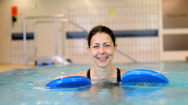 cheerful woman holding floats in swimming pool - hydrotherapy stock videos & royalty-free footage