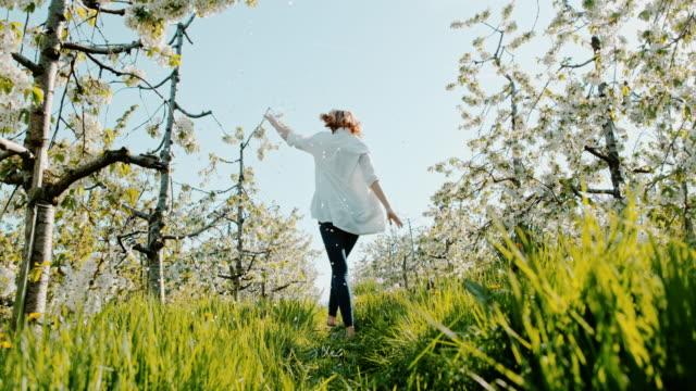桜の花の間でホッピング slo 模陽気な女性 - スキップ点の映像素材/bロール