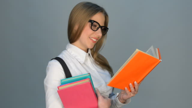 cheerful woman in glasses reading the book
