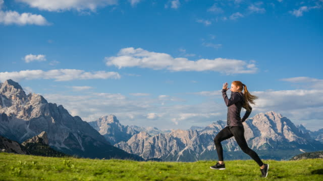 Cheerful woman jogging on a grassy meadow, mountain range in background