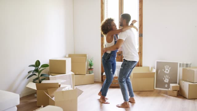 cheerful woman jumping and hugging man at home - full length stock videos & royalty-free footage