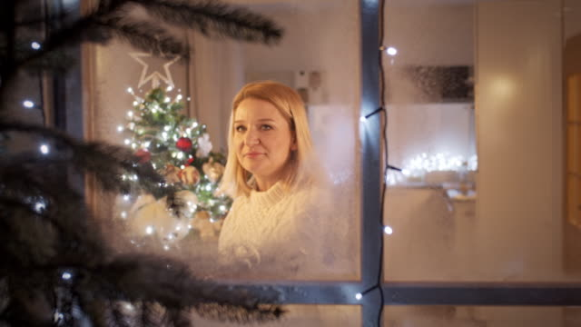 vídeos de stock e filmes b-roll de ms cheerful woman looking through a window on the christmas night - objeto decorativo