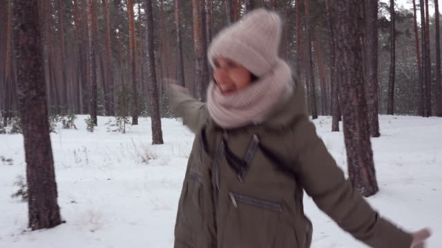 cheerful woman merrily jumping in woods, dolly shot - mitten stock videos and b-roll footage