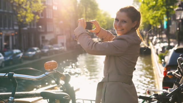 cheerful woman photographing canals of amsterdam, netherlands, smiling into camera - amsterdam stock videos & royalty-free footage