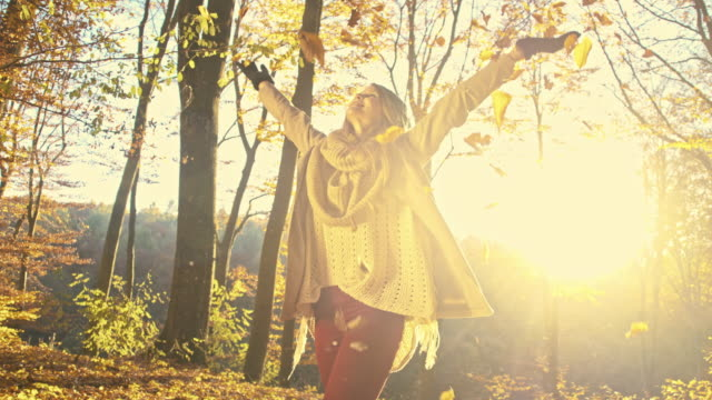 SLO MO Cheerful woman scattering dry leaves over herself